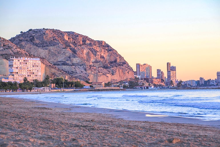 watching sunrise over rock cliff and beach things to do in alicante spain
