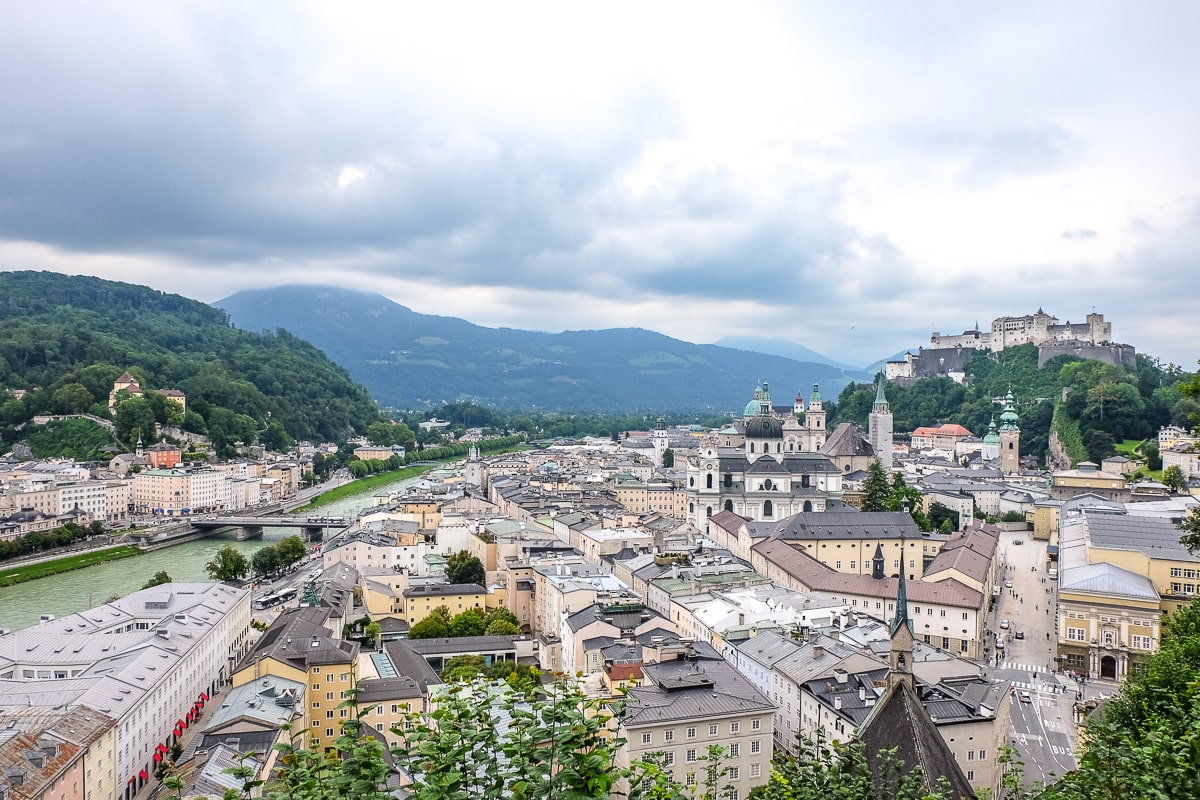 old town salzburg buildings with castle in distance from hilltop above