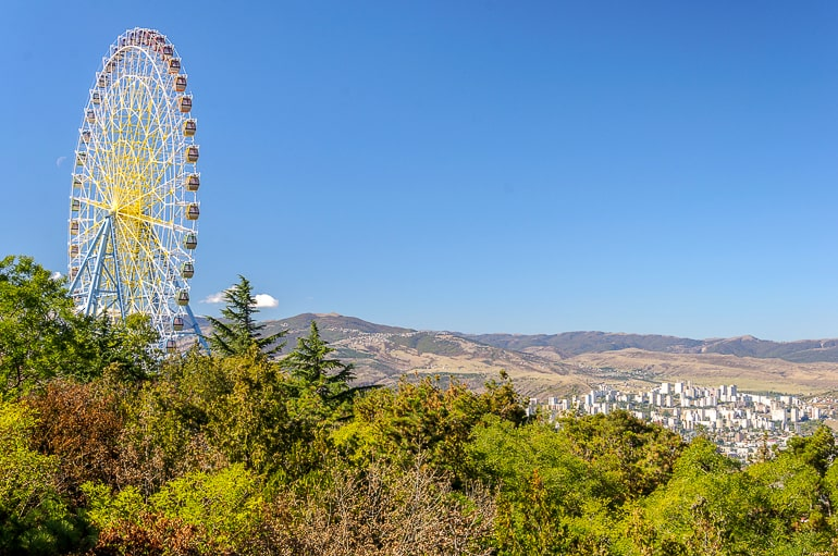 ferris wheel standing on hill surrounded by trees in tbilisi georgia
