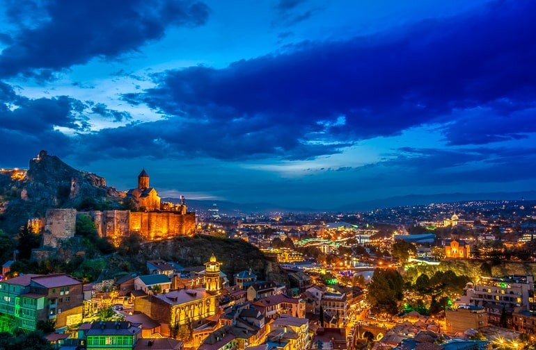 city lit up at night with church on hill in tbilisi