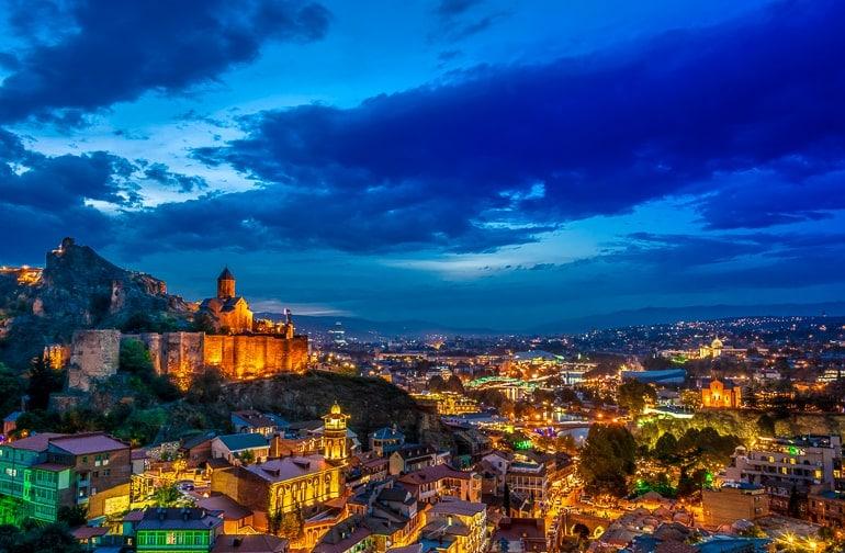 Stadt beleuchtet bei Dunkelheit mit Kirche auf dem Hügel