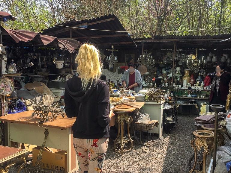 Frau läuft durch Markt im Freien mit vielen angebotenen Gegenständen
