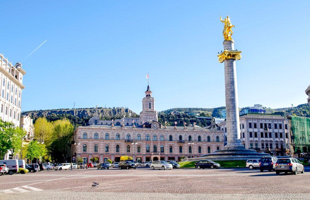 Großes Gebäude auf öffentlichem Platz mit goldener Statue