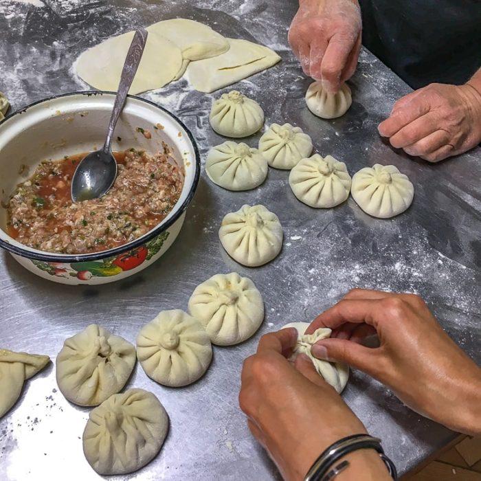 hands making dumplings on metal table with bowl beside