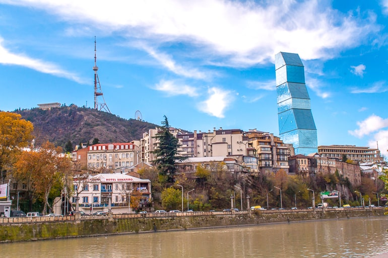 large glass hotel and tv tower on hill with river in front in tbilisi