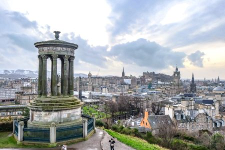 large monument with city and castle behind in edinburgh travel guide