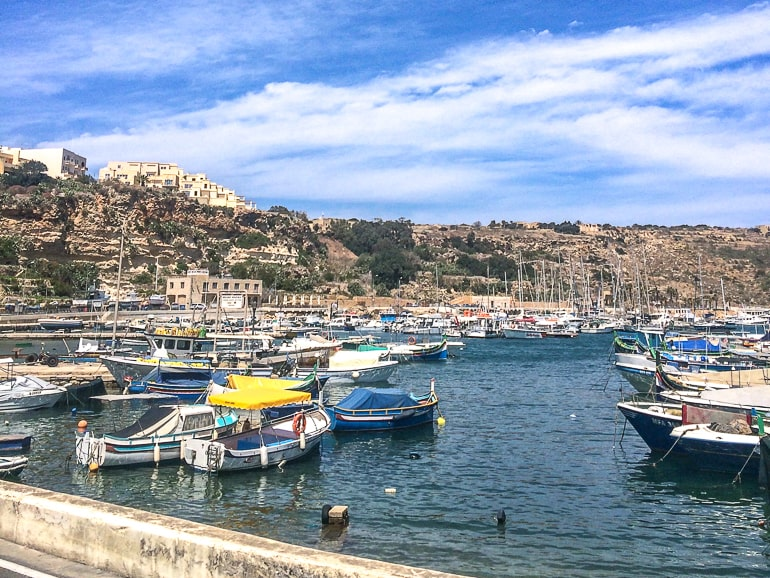 fishing boats in harbour with cliffs behind in mgarr gozo