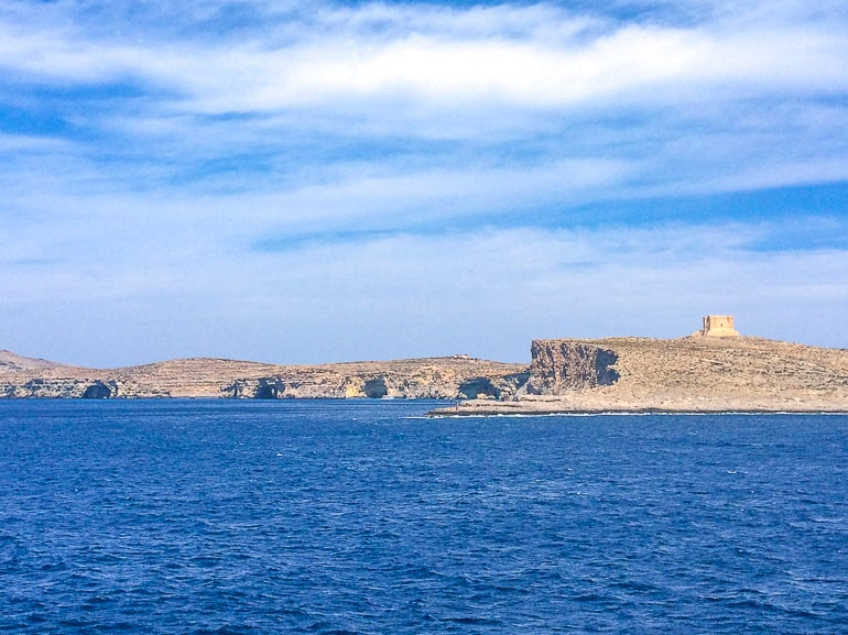 small tower on rocky cliff overlooking blue ocean channel from malta ferry
