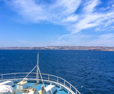 front of ferry boat with land and clouds ahead malta to gozo ferry