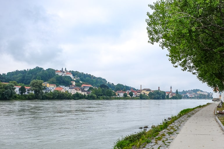 Altes Kloster auf grünem Hügel mit Weg hinauf und Fluss darunter