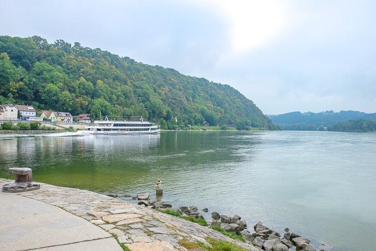 Weißes Boot auf der Donau mit grünem Gras an Ufer im Hintergrund