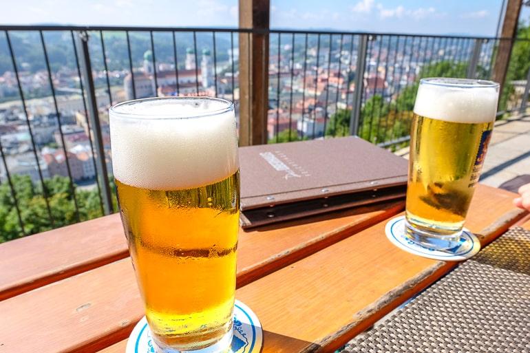 Volle Biergläser auf Holztisch mit Blick auf Stadt im Hintergrund