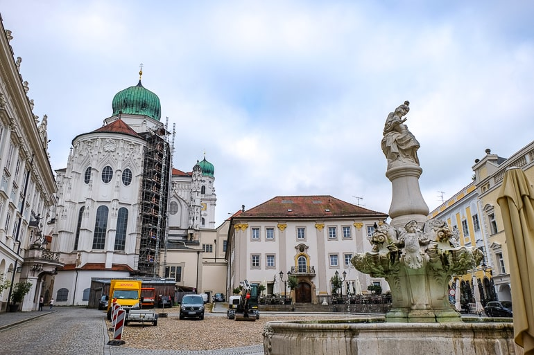 old town square with fountain and green dome in passau