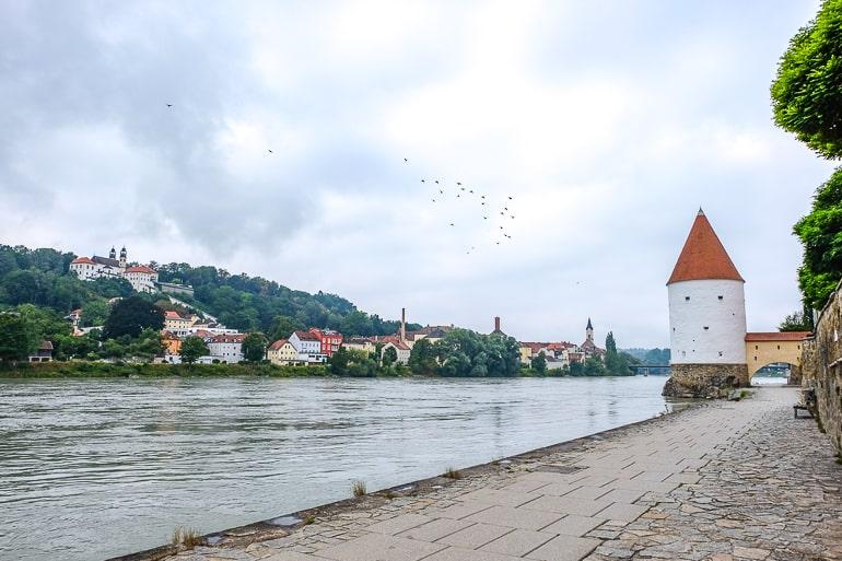 Weißer Turm mit rotem Dach neben dem Fluss in Passau
