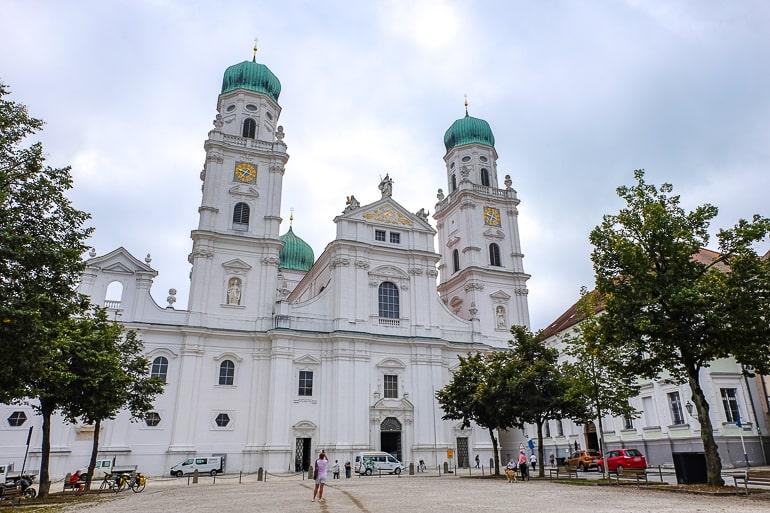 Eingang zu weißem Dom mit grünen Kuppeln in Passau