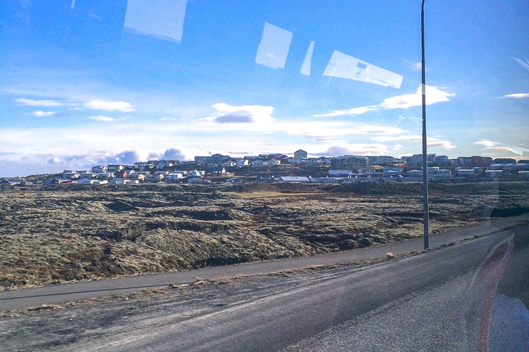 view from bus of small town on hillside in iceland