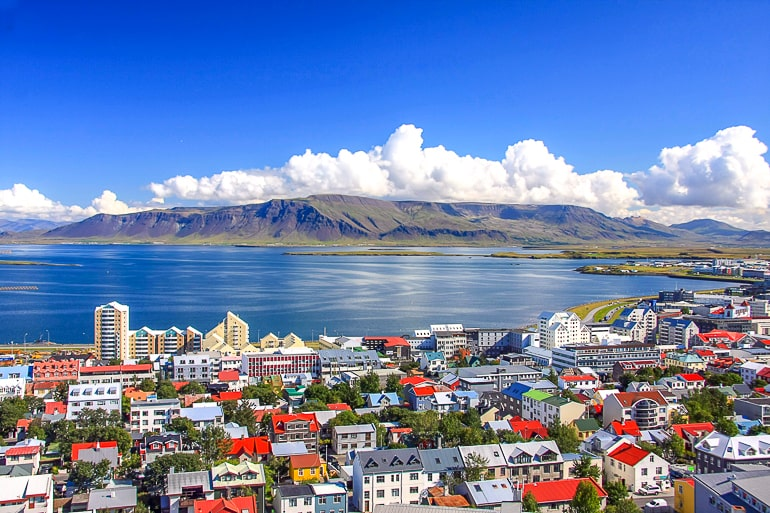 colourful rooftops in reykjavik with water and mountain in distance