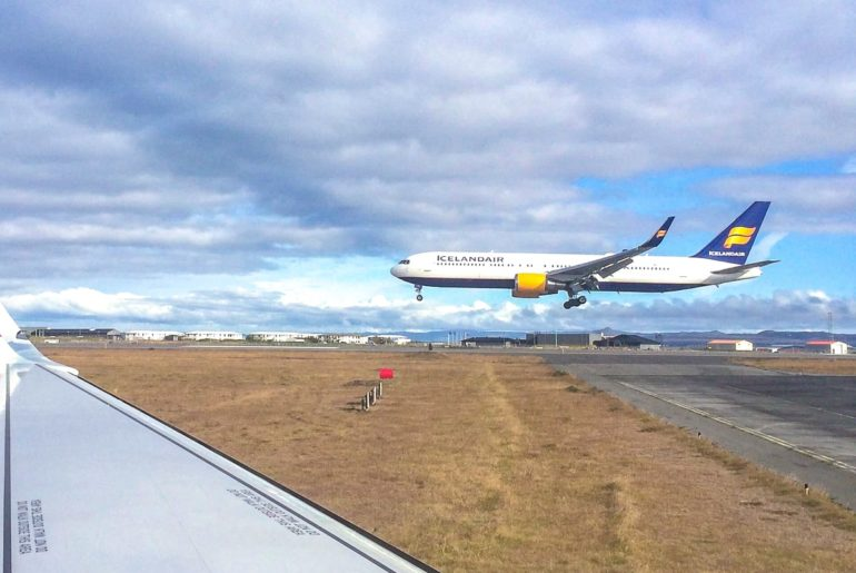 airplane landing with plane wing in front keflavik airport to reykjavik