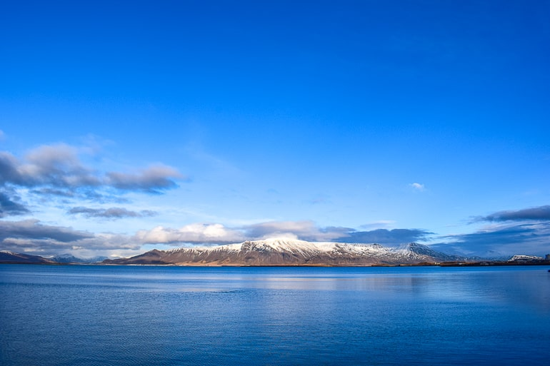 blue water in front of snowy mountain esja with blue sky in reykjavik