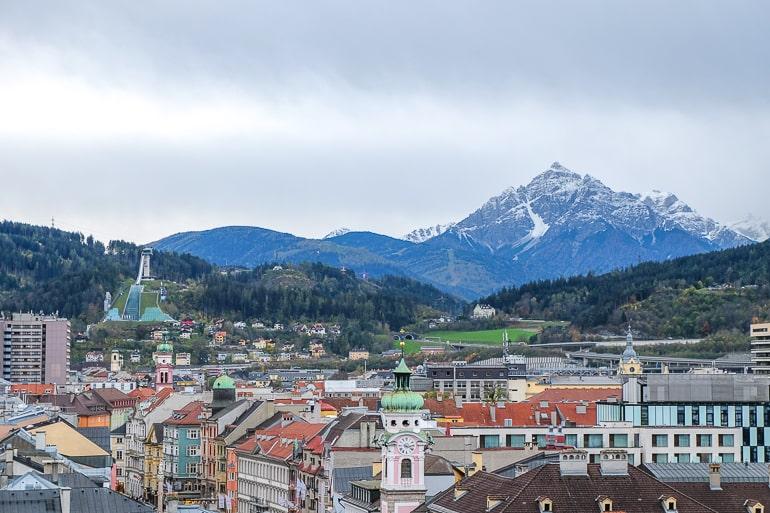 Skisprungschanze im Hintergrund mit Bergen dahinter und Gebäuden im Vordergrund