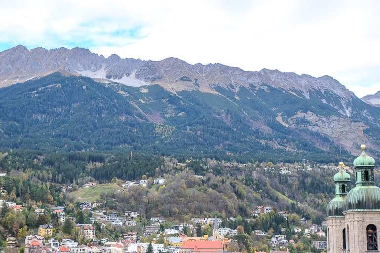 large mountain range with trees and town buildings down below in innsbruck