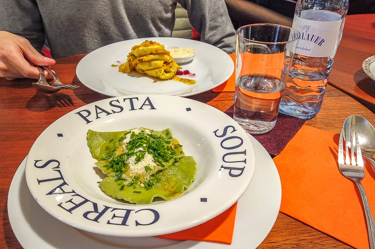 two white plates of pasta on orange table in food hall innsbruck