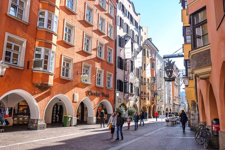 Menschen laufen neben orangenem Gebäude in Altstadt von Innsbruck