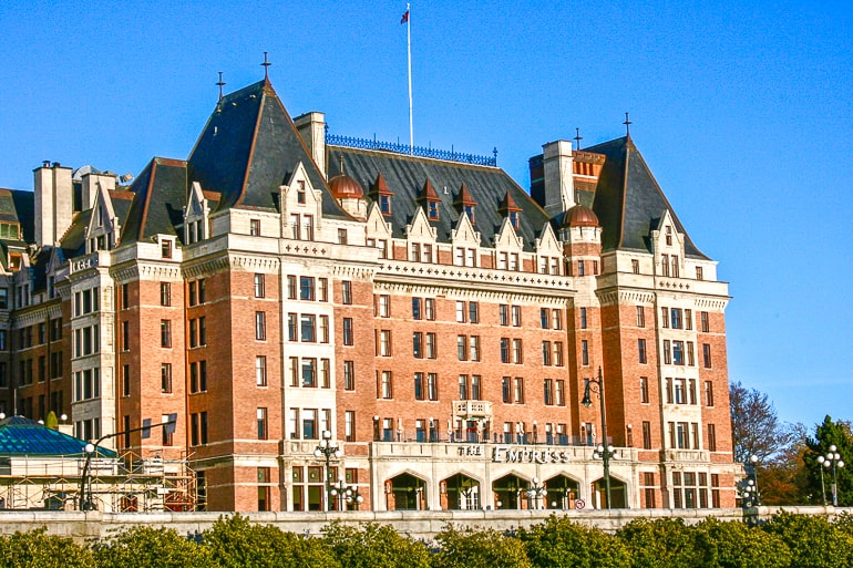 large brick hotel building with flags on top fairmont empress victoria bc