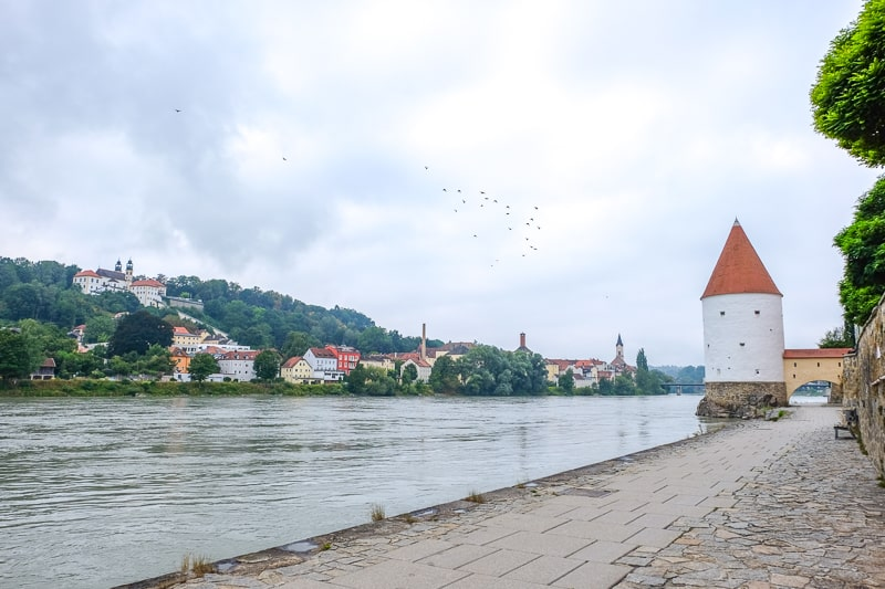 river pathway with tower and green shoreline with houses behind in distance in passau innstadt