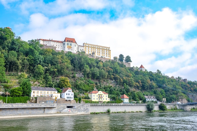 large castle up on green hillside with river below in passau