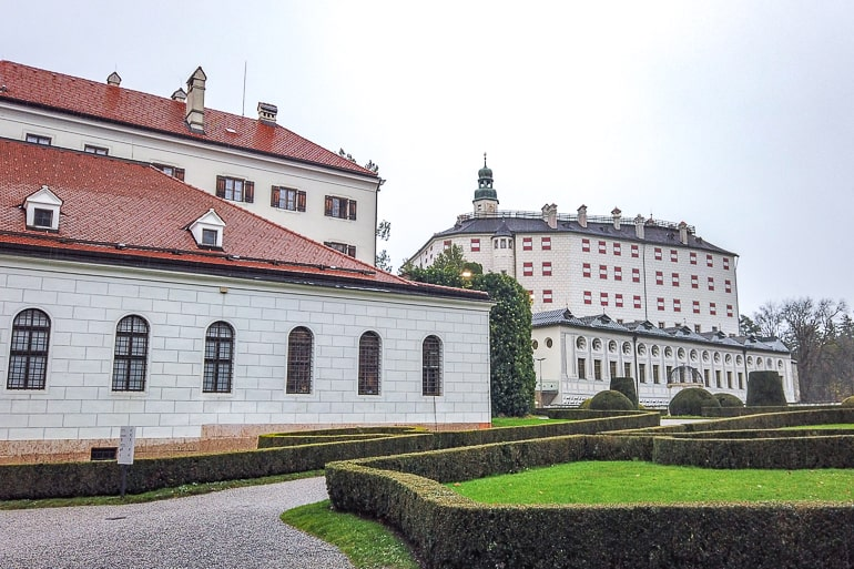 large castle and building on green garden grounds in innsbruck