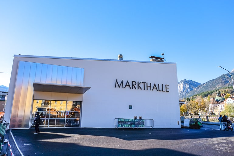 large white market hall building with parking lot in front in innsbruck