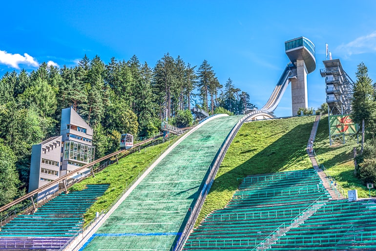 large ski jump with arena seats and green trees around in innsbruck