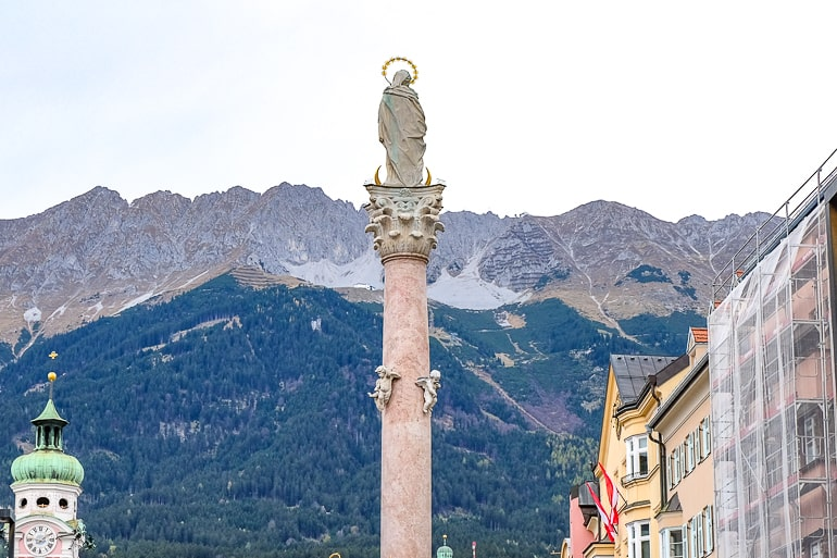 large mountain range behind close up of statue on pillar one day in innsbruck