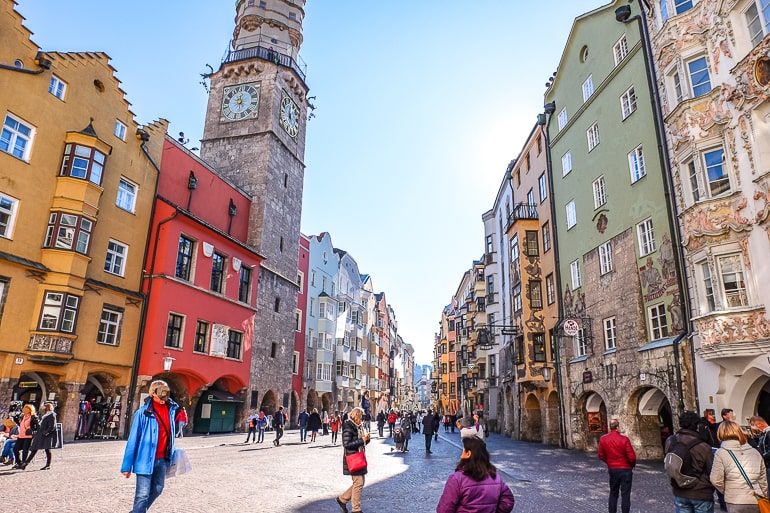 colourful old town buildings with clock tower and people shopping one day in innsbruck