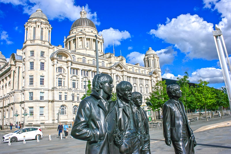 statues of the beatles in front of large building in liverpool