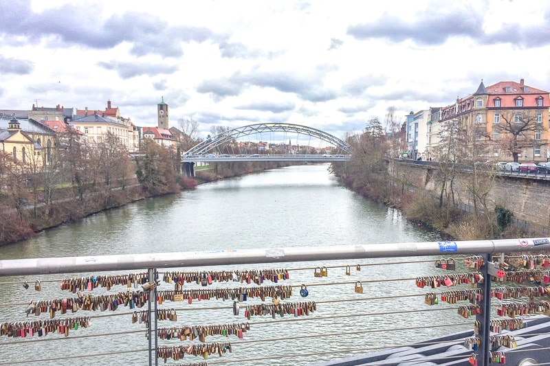 wire bridge with love locks over river in bamberg germany