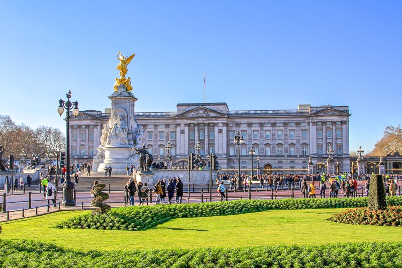 large buckingham palace with statue in front and people crowding the main gate in london