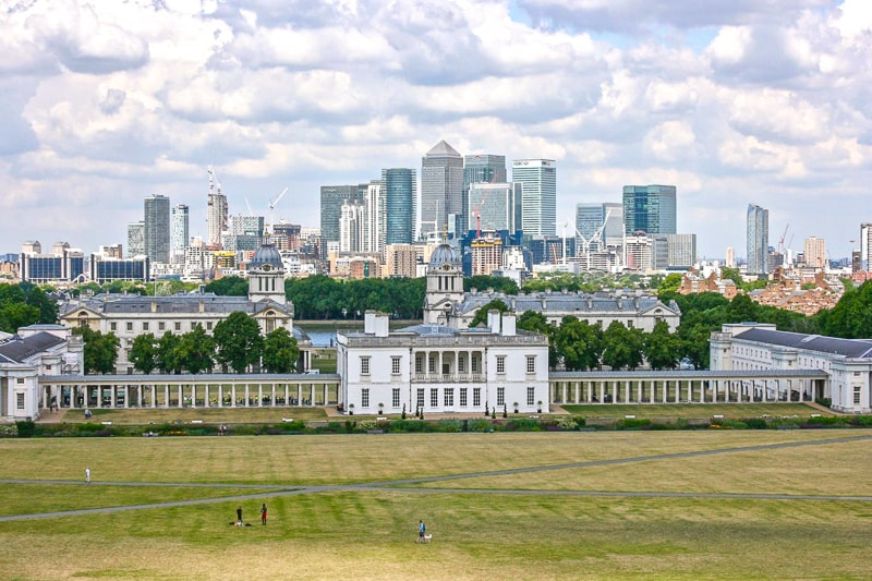 tall buildings of canary wharf london with green lawn of greenwich in front