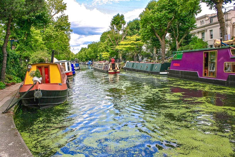 colourful boats on small canal with green scum on surface in london england