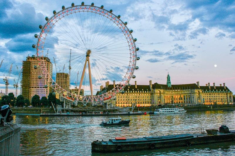 london eye bei Sonnenuntergang über dem Fluss Themse mit Booten