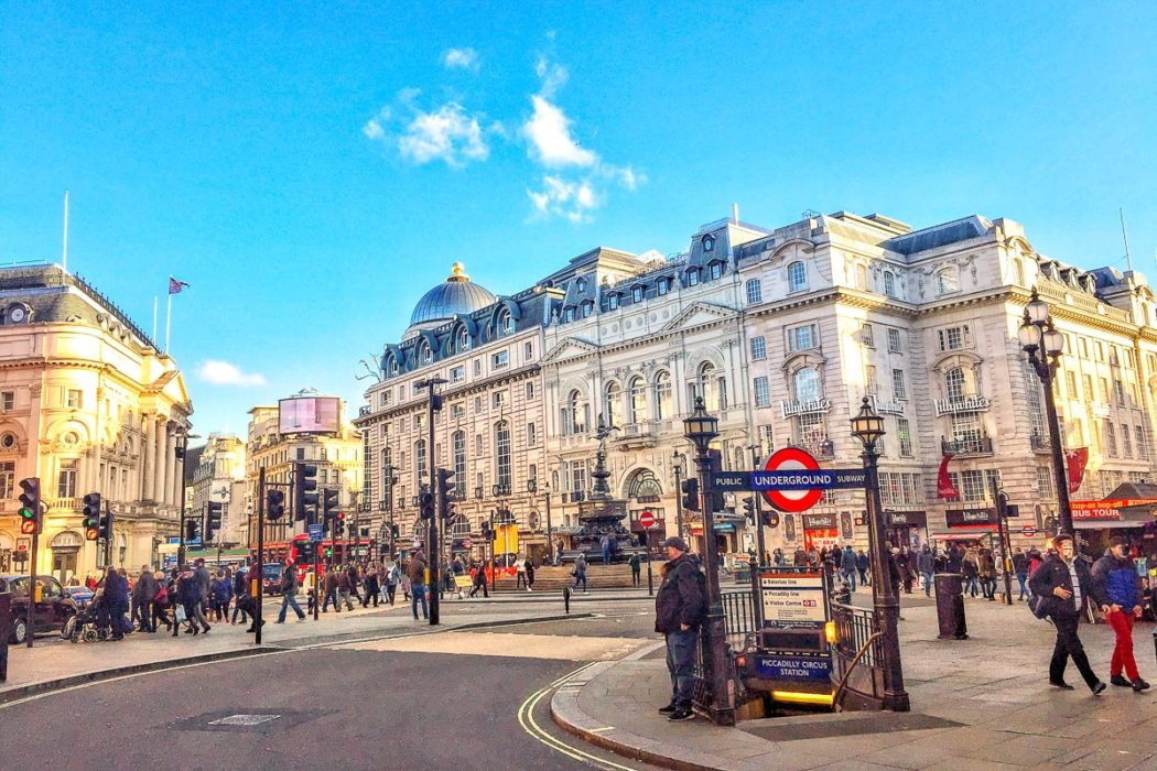 large domed building with sunshine and people crossing street in london england