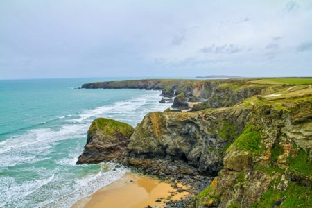 green rocky coastline of bedruthan steps places to visit along cornwall coast