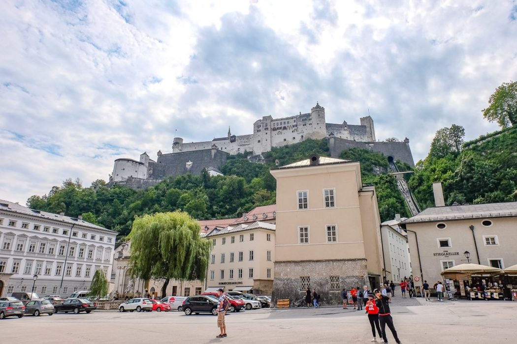 castle on hill with buildings and people below in salzburg