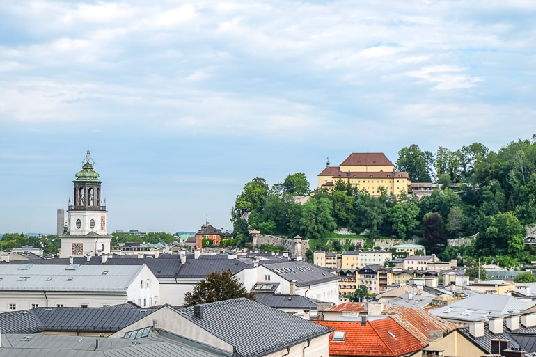 city rooftops with hilltop castle in distance in salzburg