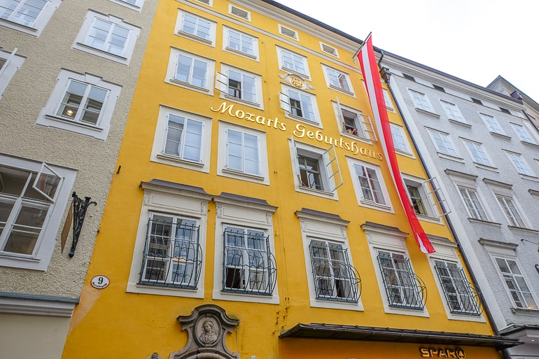 yellow building with red austrian flag hanging in front