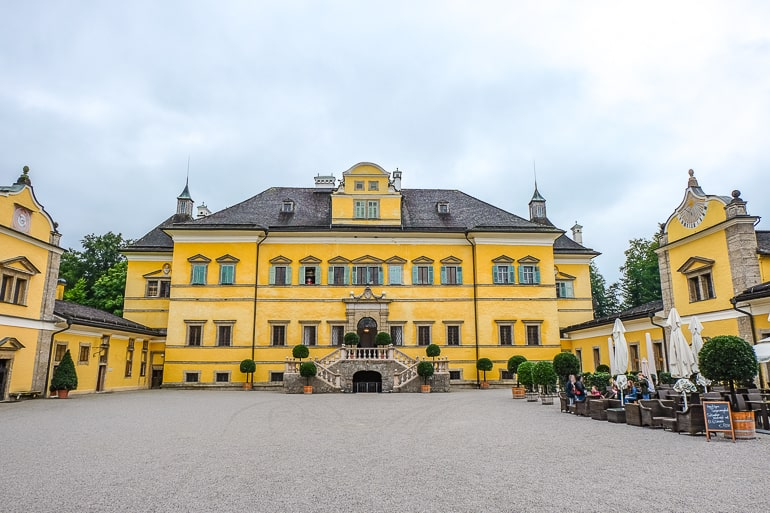 yellow palace building with courtyard and tables in salzburg