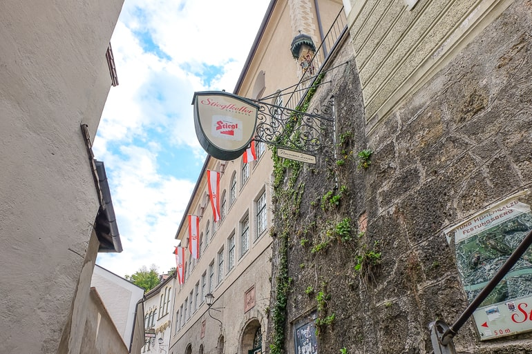 beer sign handing on wall outside old town building salzburg