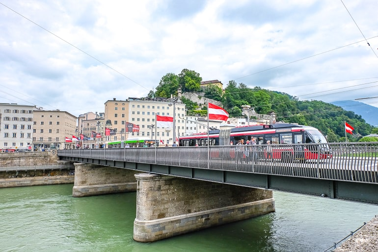 red tram crossing bridge over river in salzburg austria
