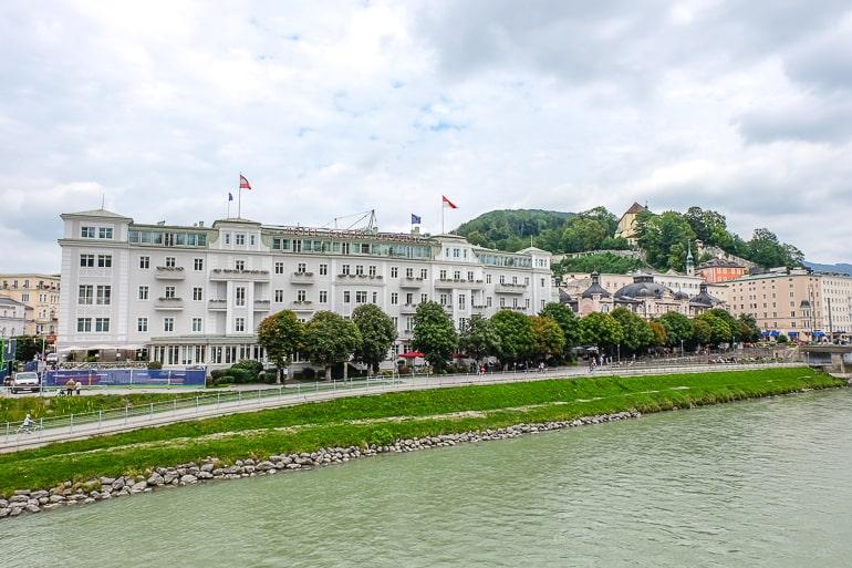 old white historic hotel on river bank in salzburg